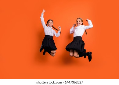 Full length body size view of two person nice attractive charming excited glad cheerful pre-teen girls having fun rejoice great accomplishment isolated over bright vivid shine orange background