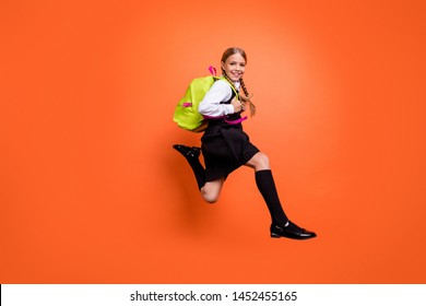 Full length body size view of nice attractive charming cheerful cheery glad pre-teen girl nerd running fast first grade motion movement isolated on bright vivid shine orange background