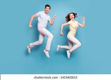Full length body size view of her she his he nice attractive lovely funny funky cheerful cheery people having fun running isolated over bright vivid shine blue green background
