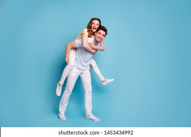 Full length body size view of his he her she nice-looking attractive cheerful cheery positive married spouses wearing casual having fun fooling isolated over bright vivid shine blue green background