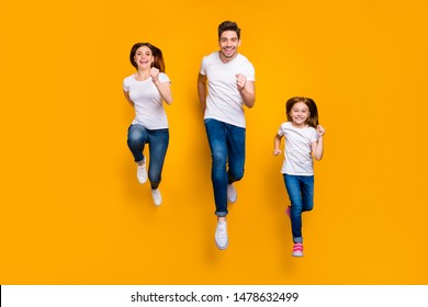 Full length body size view of three nice attractive slim fit sportive cheerful cheery person active life activity motion movement running having fun isolated over bright vivid shine yellow background