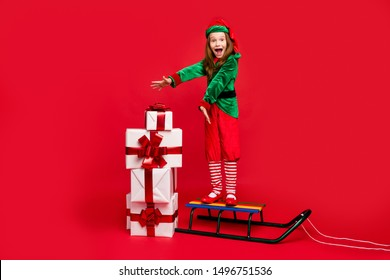 Full length body size view of nice attractive ecstatic dreamy cheerful cheery glad funny pre-teen elf standing on sled winter holly jolly tradition isolated over bright vivid shine red background