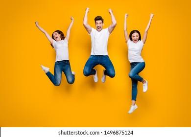 Largo retrato de vista de tamaño corporal de tres atractivos y atractivos atractivos atractivos esporádicos delgado fuerte sporto satisfecho alegre persona alegre que se divirtió aislado sobre el brillante brillo de fondo amarillo