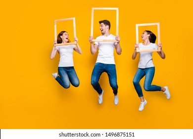 Full length body size view portrait of three nice attractive cheerful cheery glad excited person holding in hands frames having fun good funny mood isolated over bright vivid shine yellow background