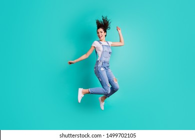 Full length body size view of her she nice attractive cheerful cheery glad carefree girl wearing overall jumping having fun free time isolated on bright vivid shine vibrant green turquoise background