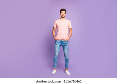 Full length body size view of his he nice attractive fit peaceful content guy wearing pink tshirt standing straight holding hands in pockets isolated on violet purple lilac pastel color background