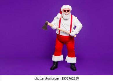 Full length body size view of his he nice funky hilarious cheery glad cheerful bearded thick fat dangerous Santa holding in hands ax isolated over bright vivid shine vibrant violet lilac background