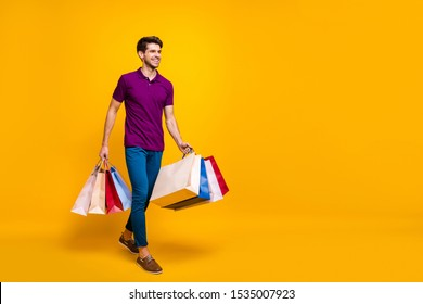Full length body size view of his he nice attractive cheerful cheery guy carrying new things clothing packages isolated over bright vivid shine vibrant yellow color background