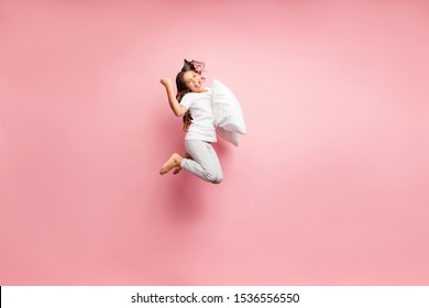 Full length body size view of nice attractive lovely cute childish playful cheerful cheery wavy-haired pre-teen girl jumping with soft pillow having fun isolated over pink pastel color background