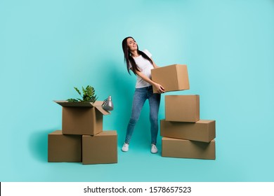 Full length body size view of nice attractive sad exhausted brunet girl moving abroad holding carrying big large box isolated on bright vivid shine vibrant teal green blue turquoise color background