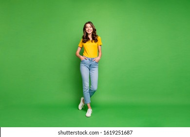 Full length body size view of her she nice attractive lovely cheerful cheery content wavy-haired girl holding hands in pockets isolated over bright vivid shine vibrant green color background