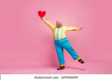Full length body size view of his he nice funky crazy dreamy positive glad bearded guy having fun holding in hand heart shape celebrating isolated over pink pastel color background