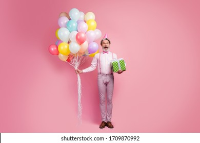 Full length body size view of nice attractive well-dressed elegant glad cheerful grey-haired man holding in hands bunch air balls giftbox delivery isolated over pink pastel color background