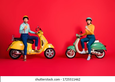 Full length body size view of her she his he nice attractive amazed stunned friends friendship sitting on moped using 5g web service app isolated on bright vivid shine vibrant red color background