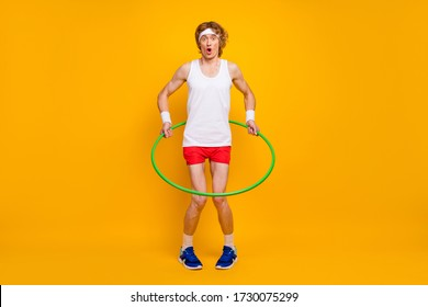 Full length body size view of nice funky slim thin comic childish foolish guy spinning plastic circle around waist having fun isolated over bright vivid shine vibrant yellow color background