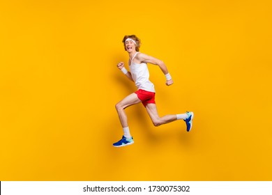 Full length body size view of nice funky glad excited cheerful cheery motivated guy jumping running fast hurry rush marathon isolated over bright vivid shine vibrant yellow color background