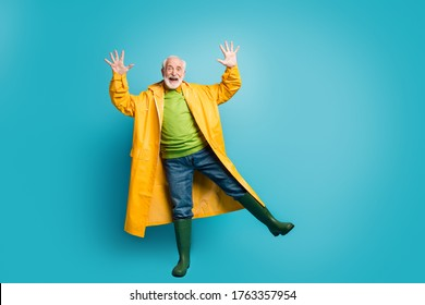 Full length body size view of his he nice cheerful cheery positive grey-haired man wearing yellow overcoat dancing having fun time isolated over bright vivid shine vibrant blue color background