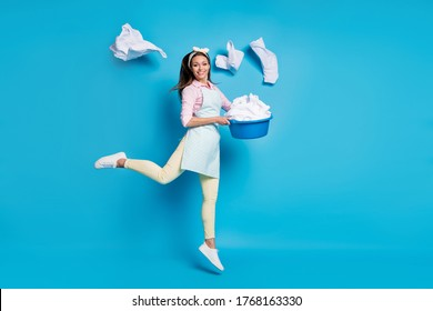 Full length body size view of her she nice attractive cheerful cheery girl maid jumping holding in hand laundry bowl throwing things isolated on bright vivid shine vibrant blue color background