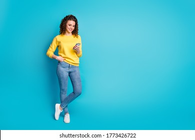 Full length body size view of her she nice attractive focused cheerful wavy-haired girl walking using device browsing media multimedia isolated over bright vivid shine vibrant blue color background