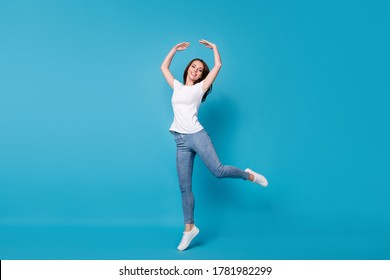 Full length body size view of her she attractive pretty skinny cheerful cheery girl jumping having fun dancing ballet practicing isolated bright vivid shine vibrant blue color background