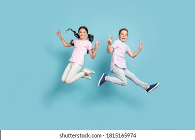 Full length body size view of her she his he nice attractive small little cheerful cheery friends friendship kids jumping showing v-sign having fun isolated over blue pastel color background