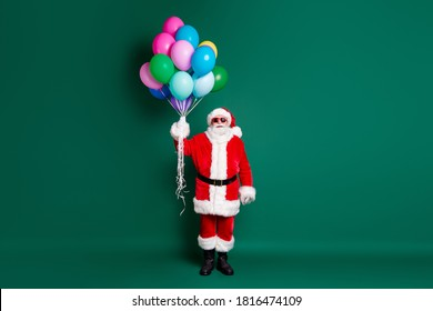 Full length body size view of his he nice attractive handsome Santa father holding in hands bunch air helium balls celebratory festal occasion isolated over green color background