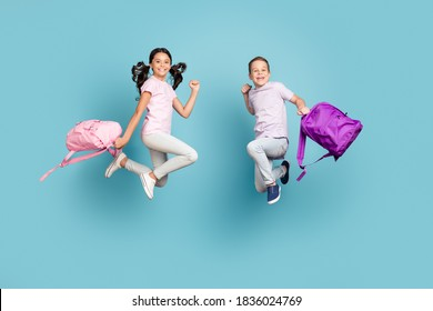 Full length body size view of his he her she nice attractive small little cheerful buddy, fellow jumping having fun after classes leisure autumn fall season isolated blue pastel color background - Shutterstock ID 1836024769