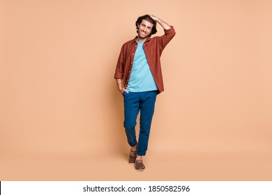 Full length body size view of attractive cheerful guy caressing hair walking isolated over beige pastel color background
