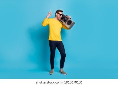 Full length body size view of nice cool carefree cheerful guy carrying player having fun isolated over bright blue color background