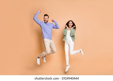 Full length body size view of nice cheerful lucky partners couple jumping having fun isolated on beige pastel color background - Shutterstock ID 1924940444