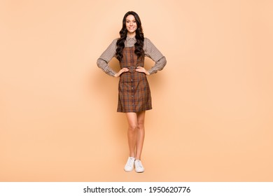 Full length body size view of lovely cheery content wavy-haired girl wear checked uniform hands on hips isolated on beige pastel color background
