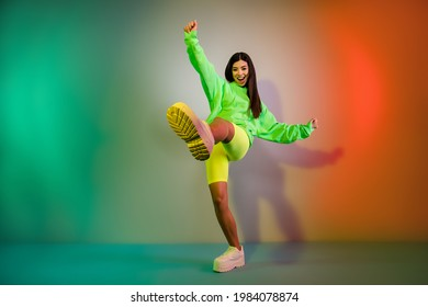 Full length body size view of pretty funky cheerful girl dancing good mood isolated over multicolor vivid neon light background