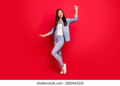 Full length body size view of attractive cheerful carefree girl having fun dancing isolated over bright red color background