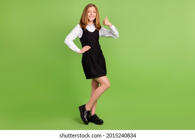 Full length body size view of attractive cheerful girl showing thumbup ad isolated over bright green color background