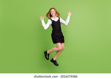 Full length body size view of attractive cheerful carefree girl jumping dancing isolated over green color background