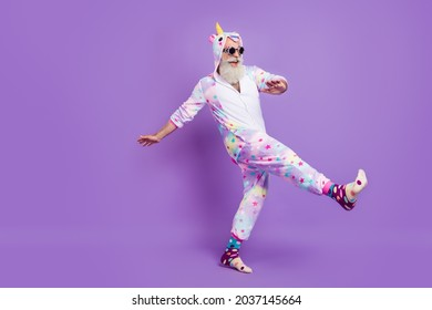 Full length body size view of nice funny cheerful man in pajama walking having fun isolated over violet purple color background