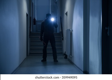Full length of burglar with flashlight and crowbar in office corridor