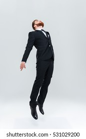 Full length business man in black suit flying or jumping in studio. Isolated gray background
