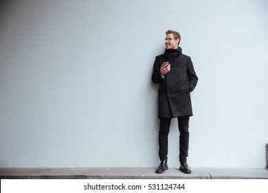 Full length business man in glasses and warm clothes standing near the wall with phone and looking aside