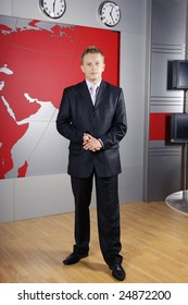 full length business man standing up in front of the camera in television news studio