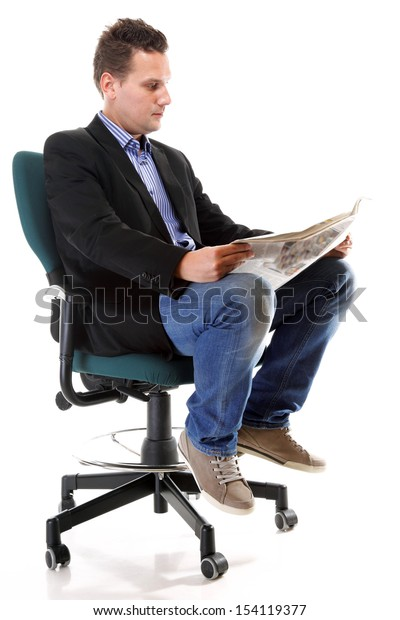 Full length businessman sitting on chair reading a newspaper isolated on white background