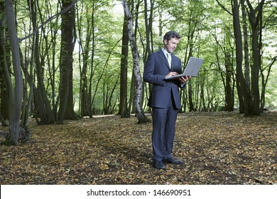 Full length of businessman using laptop in middle of forest
