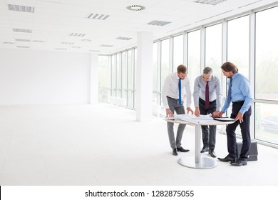 Full length of businessmen discussing over blueprints at table in new office