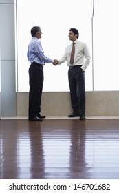 Full length of businessmen shaking hands in office