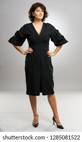 Full length of a businesswoman in black dress over gray background