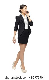 Full length of businesswoman walking talking on mobile phone, isolated on white background