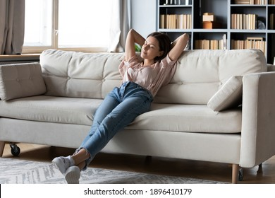 Full length calm woman with closed eyes resting on cozy couch, leaning back, enjoying lazy leisure time, attractive peaceful young female relaxing, daydreaming, taking nap on sofa at home