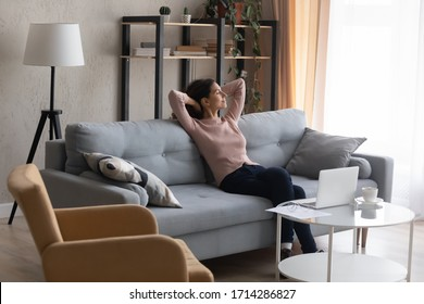 Full length carefree young attractive caucasian woman resting on sofa with closed eyes. Calm millennial female freelancer businesswoman enjoying break pause time, working from home online on computer.