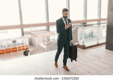 Full length of Caucasian bearded businessman with serious face using smart phone, carrying luggage and walking on the train station. Business trip concept.