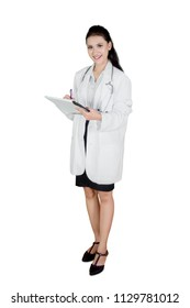 Full length of Caucasian female doctor is writing on a clipboard, isolated on white background